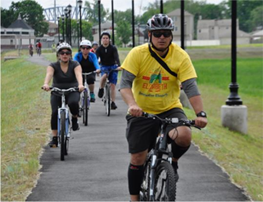 Men and women biking along a path with a tour guide wearing a yellow Elizabeth tour shirt