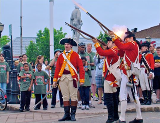 Men dressed up as English red coats firing muskets